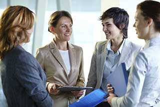 Women dressed in business attire meeting at work