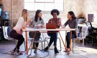 4 women meeting round a table in an office